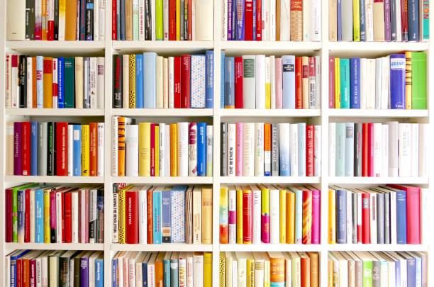 White library book shelves packed with colorful books stock photo