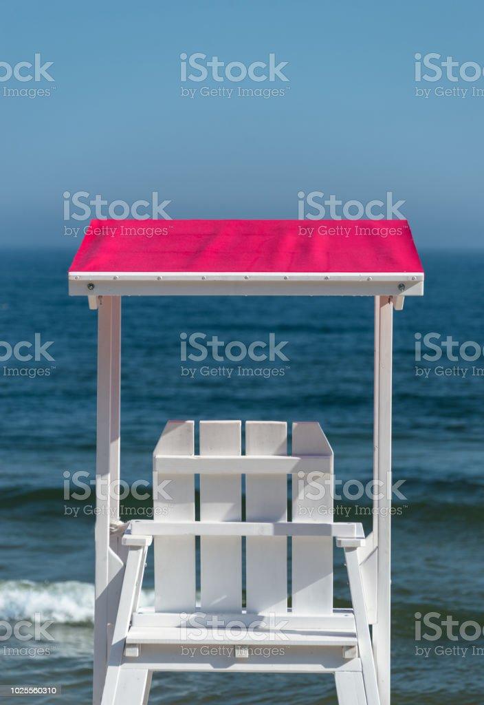 Weiße Rettungsschwimmer Stuhl sichtbar von der Rückseite mit einem rosa Visier vor dem Hintergrund eines schönen blauen Meer und Himmel an einem sonnigen Sommertag. – Foto