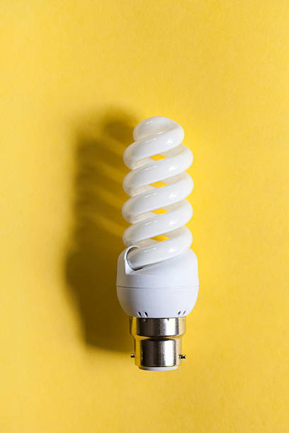 White light bulb isolated on a yellow background. stock photo
