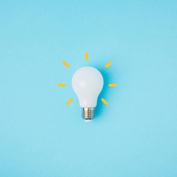 ampoule blanche avec des lignes jaunes isolées sur bleu - imitant un animal photos et images de collection