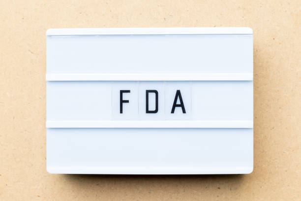 white lightbox with word fda (abbreviation of food and drug administration) on wood background - fda stock photos and pictures