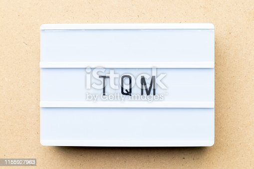 White lightbox with word TQM (Abbreviation of total quality management) on wood background