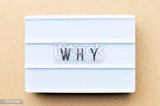 White lightbox with word why on wood background