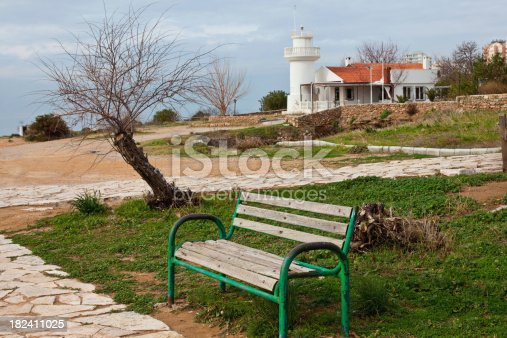 182421396 istock photo White Lighthouse Behind The Green Bench 182411025