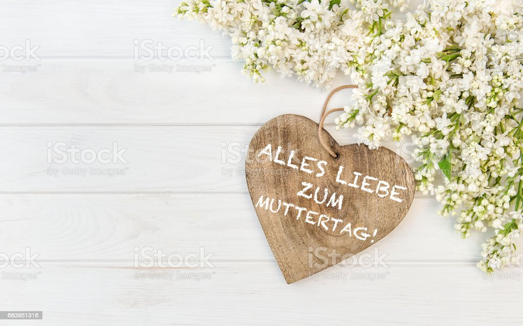 White lilac flowers wooden heart Mothers Day german stock photo