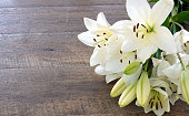 istock White Lily flowers on wooden background 1282096956