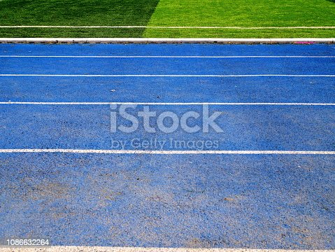 istock White line between green grass football field and bluetrack runway 1086632264