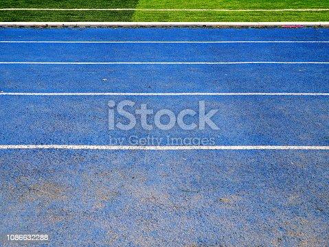 istock White line between green grass football field and bluetrack runway 1086632288