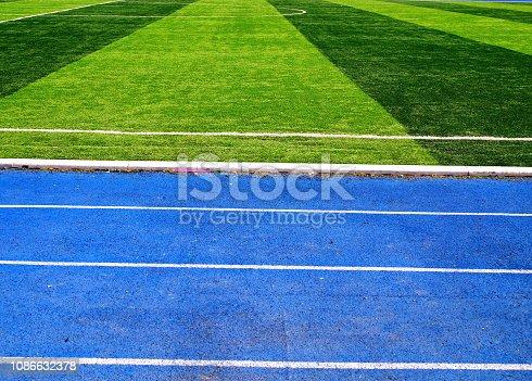 istock White line between green grass football field and bluetrack runway 1086632378