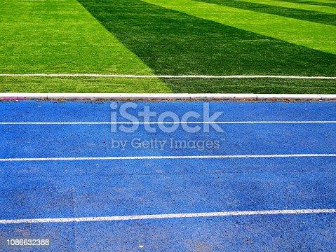 istock White line between green grass football field and bluetrack runway 1086632388