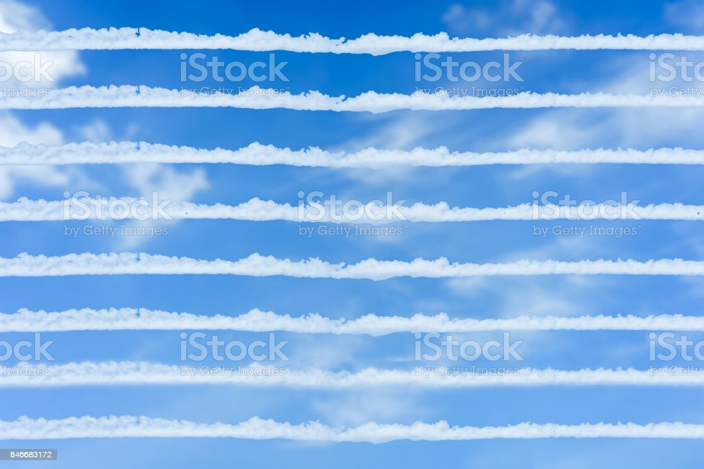 White lined blank on the sky for text and background usage. Traces or vapour of Jet aircraft rises to the bright blue sky. White fluffy clouds in the blue sky. stock photo
