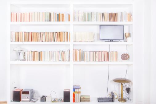 white living room with modern wooden bookshelf