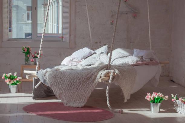 weiße loft interieur im klassischen skandinavischen stil. hängenden bett von der decke abgehängt. gemütliche große gefaltete beige kariert, riesige decke stricken, stricken zu bewaffnen. trendige raumgestaltung - teppich baumwolle stock-fotos und bilder