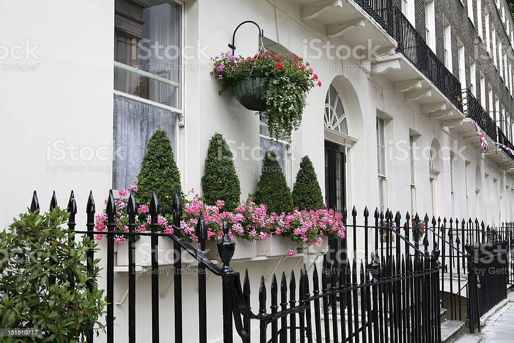 White London townhouses with potted plants and a black fence stock photo