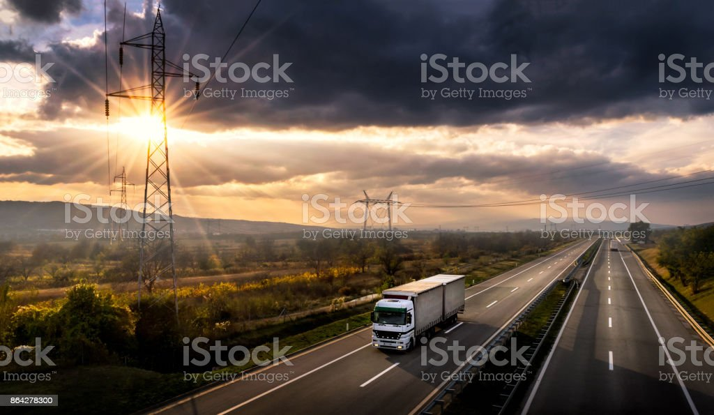 White lorry on a highway at sunset royalty-free stock photo
