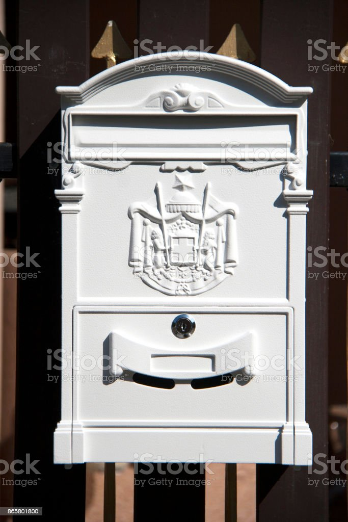 White mailbox on the brown and gold fence. stock photo