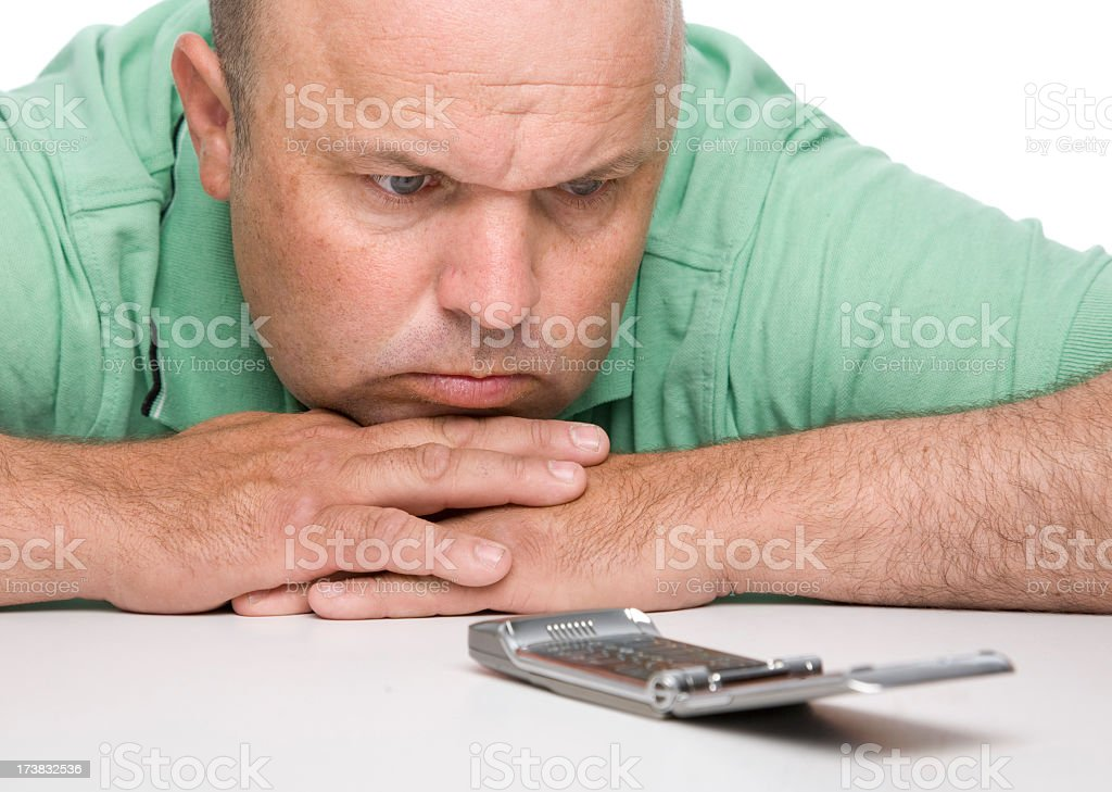 White man resting chin on hands looking at open flip phone royalty-free stock photo