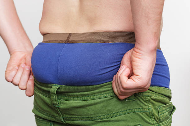 White man trying to pull his pants on fat ass stock photo