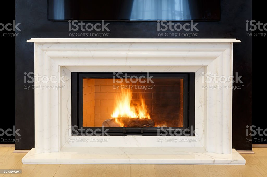 white, marble fireplace and burning fire. stock photo