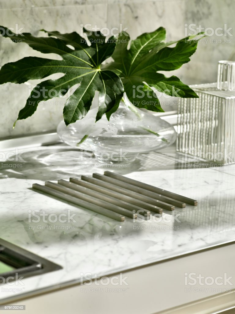ガラス花瓶と、大きな白い大理石キッチン細部葉します。 ストックフォト