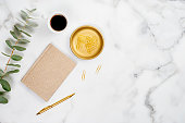 istock White marble office desk table with gold paper notebook, eucalyptus leaf, pen, cup of coffee and stationery. Flat lay, top view. 1192899901