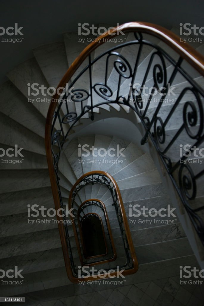 Soft light shines in at each floor of a light marble staircase with...