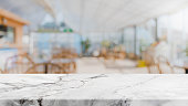 istock White marble stone table top and blurred restaurant interior background 911901398