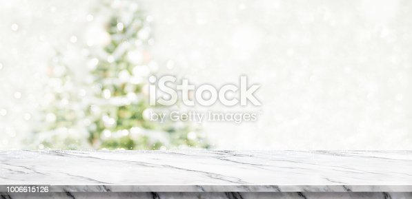 1136239089 istock photo White marble table top at blur bokeh christmas tree decor with string light background when show falling,Winter holiday greeting card. 1006615126