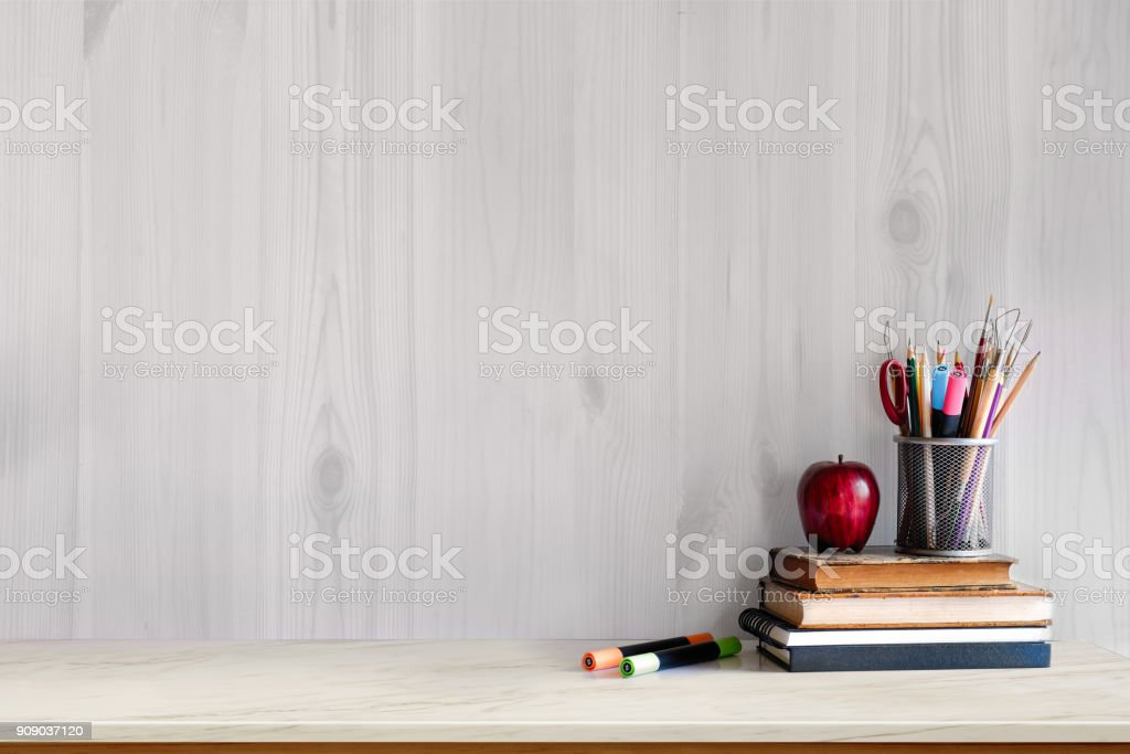 White marble table with vintage books, red fruit and supplies. Workspace with copy space for products display montage. mock up concept. royalty-free stock photo
