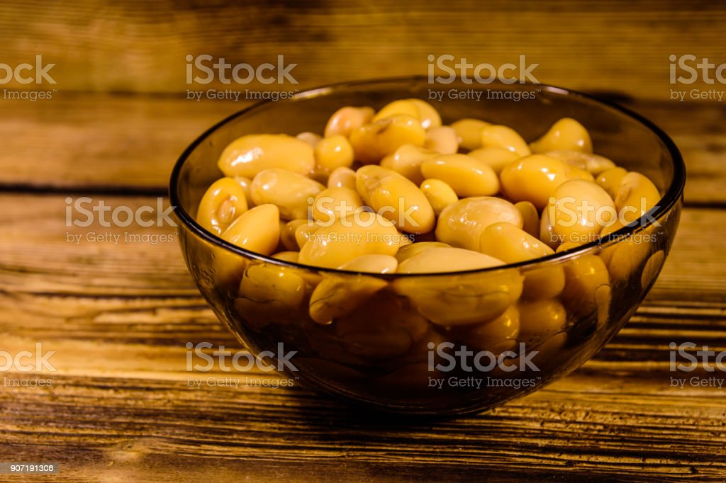 White marinated haricot beans in glass bowl on a wooden table stock photo