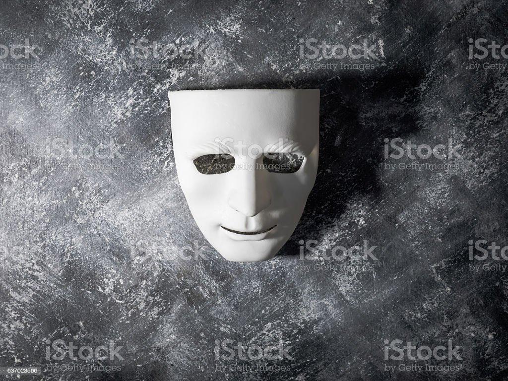 White mask on gray grunge background. stock photo