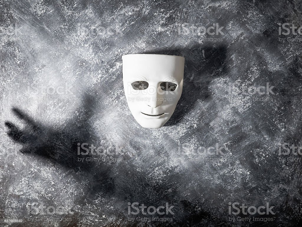 White mask with shadow of hand on gray grunge background. stock photo