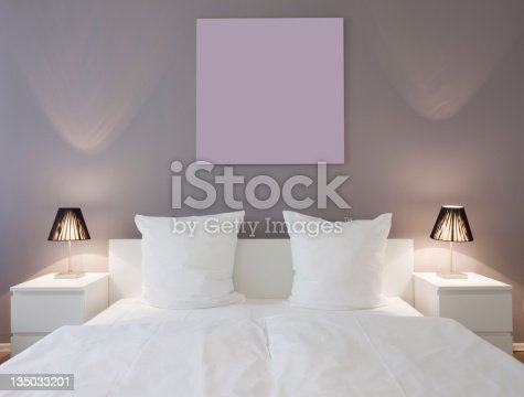King bed with white sheets, pillows and bed side lamps on dressers.
