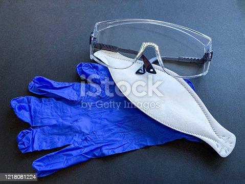 white medical mask protective PPE2.  protective transparent glasses.  blue gloves.  Black background.