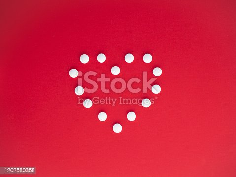 istock White medicine pills in the shape of a heart on a red background top view with copy space. 1202580358