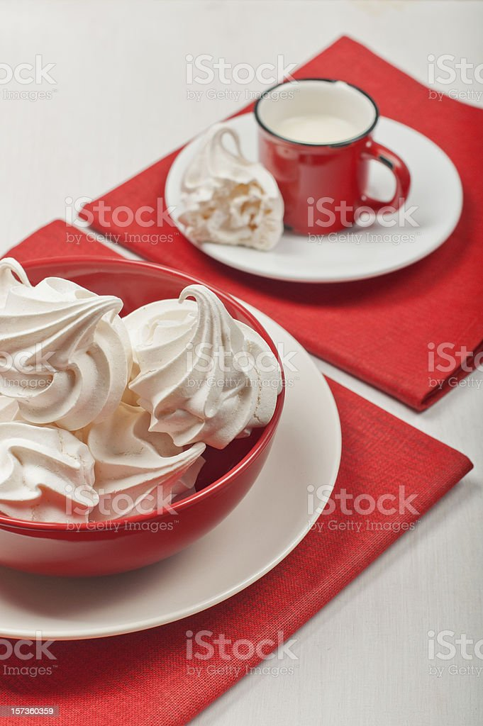 White meringues and a red cup with milk. royalty-free stock photo