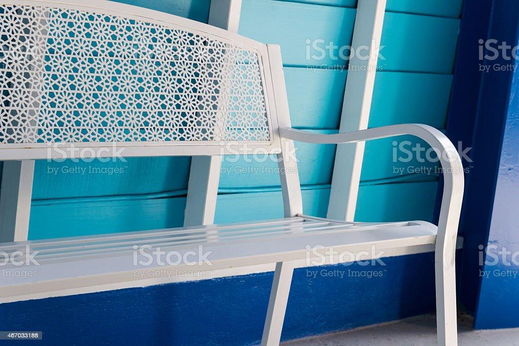 white metal seat beside blue wall stock photo