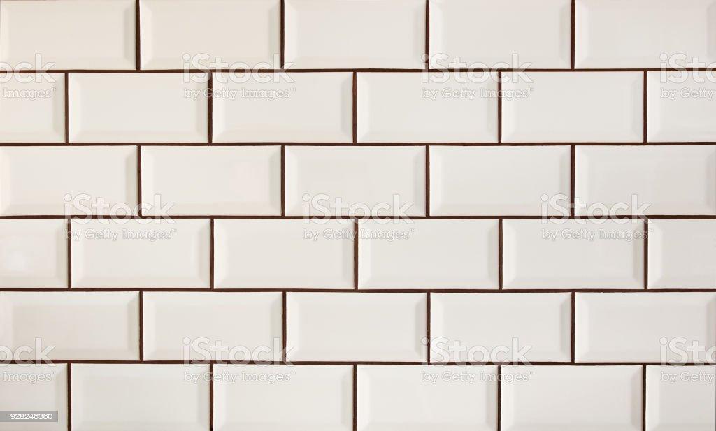 White metro tiles patterned wall. Beige ceramic brick tiles background. stock photo