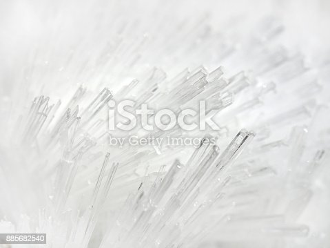 White mineral crystals cluster. Macro image of  Quartz needle crystal cluster on rock matrix, tubular structure. White textured and background