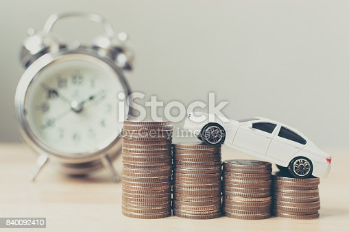 istock White miniature car on money coin stack growth with clock 840092410
