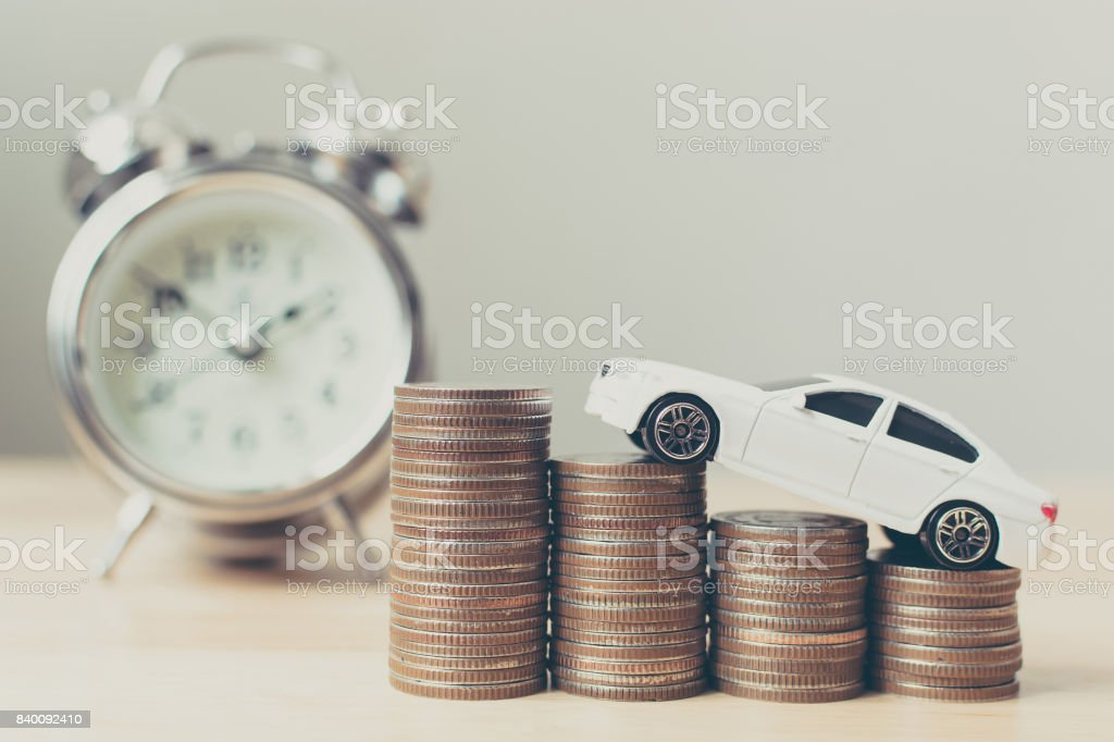 White miniature car on money coin stack growth with clock stock photo