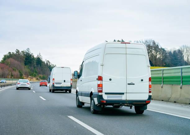 weiße minivans unterwegs - van stock-fotos und bilder