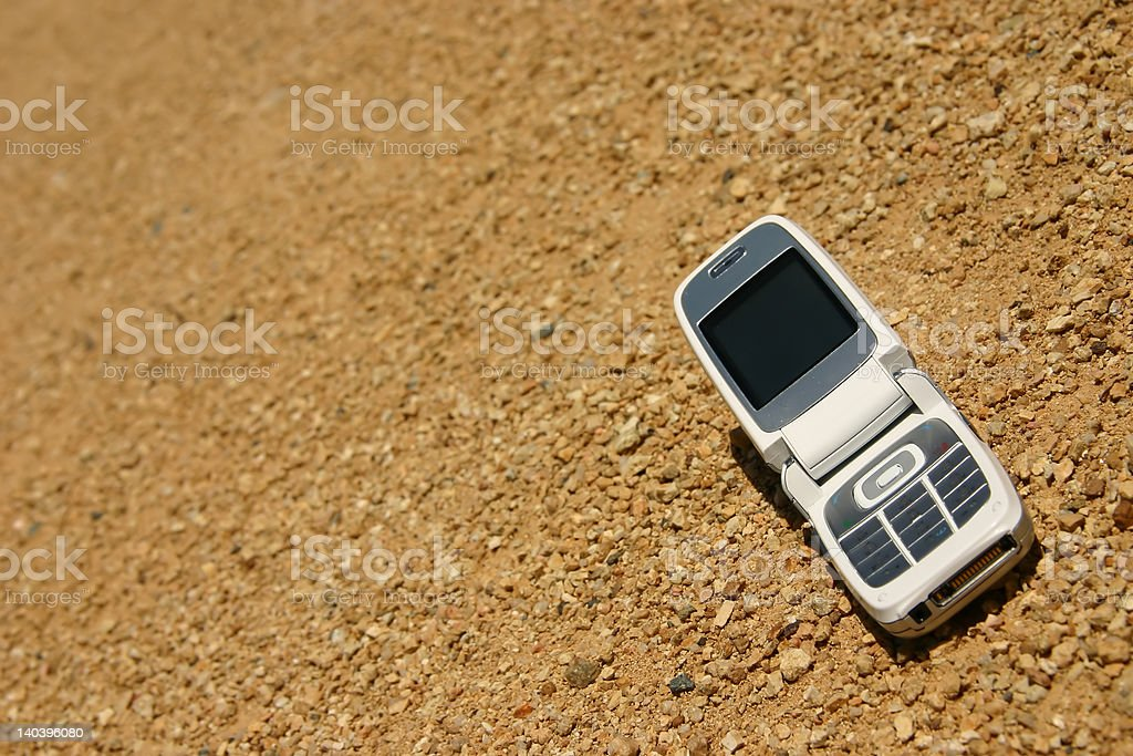 White mobile cell phone in the desert royalty-free stock photo