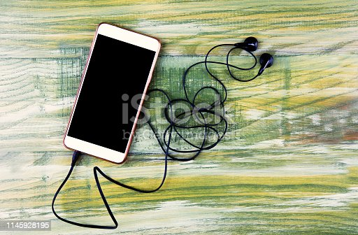 istock White mobile phone and earphone on wooden background 1145928195