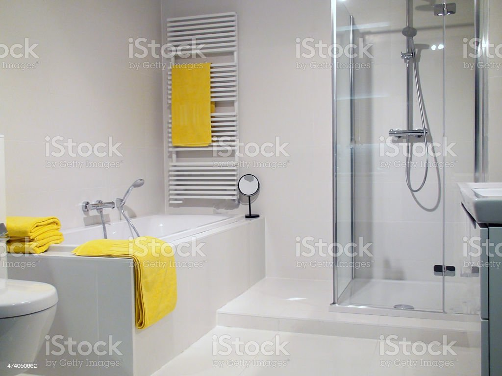 White modern bathroom with yellow towels and shower cubicle stock photo
