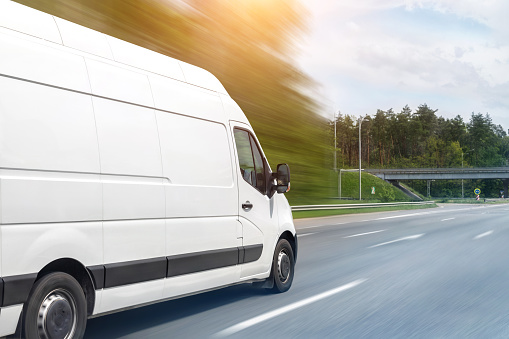 White modern delivery small shipment cargo courier van moving fast on motorway road to city urban suburb. Busines distribution and logistics express service. Mini bus driving on highway on sunny day.