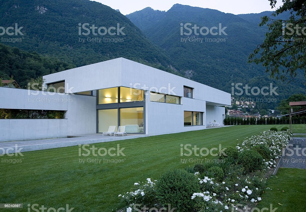 White modern house in the mountains at dusk royalty-free stock photo