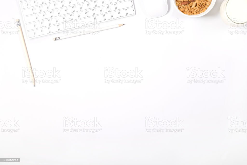 White modern keyboard, mouse, pencils, plate with granola and glass of milk on white background. Light minimal mockup. Concept of healthy lifestyle. Top view. stock photo