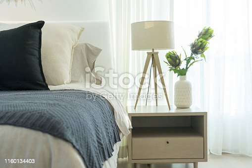 White modern lamp in cozy bedroom with dark blue blanket on it in bedroom interior