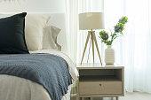 White modern lamp in cozy bedroom with dark blue blanket on it in bedroom interior